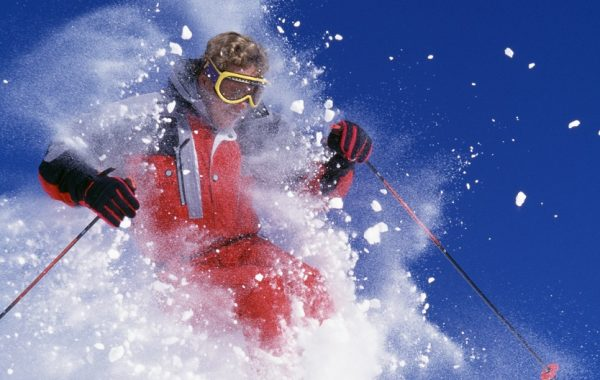 Man Snow Skiing Over Mogul Through Fresh Powder Snow.